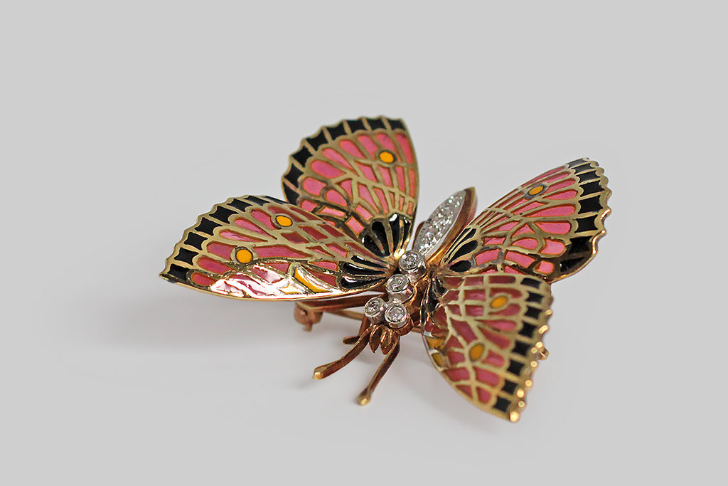 A big, beautiful, vintage butterfly brooch, modeled in 18k yellow gold, whose shapely, articulate wings are decorated with translucent, plique-à-jour enamel, in three colors— an earthy pink, a rich golden yellow, and true black. Plique-à-jour enamel is beloved for its glowing, stained-glass-like effect. Our butterfly's body is topped with applied, white gold mounts that hold both bead and bezel set brilliant-cut diamonds