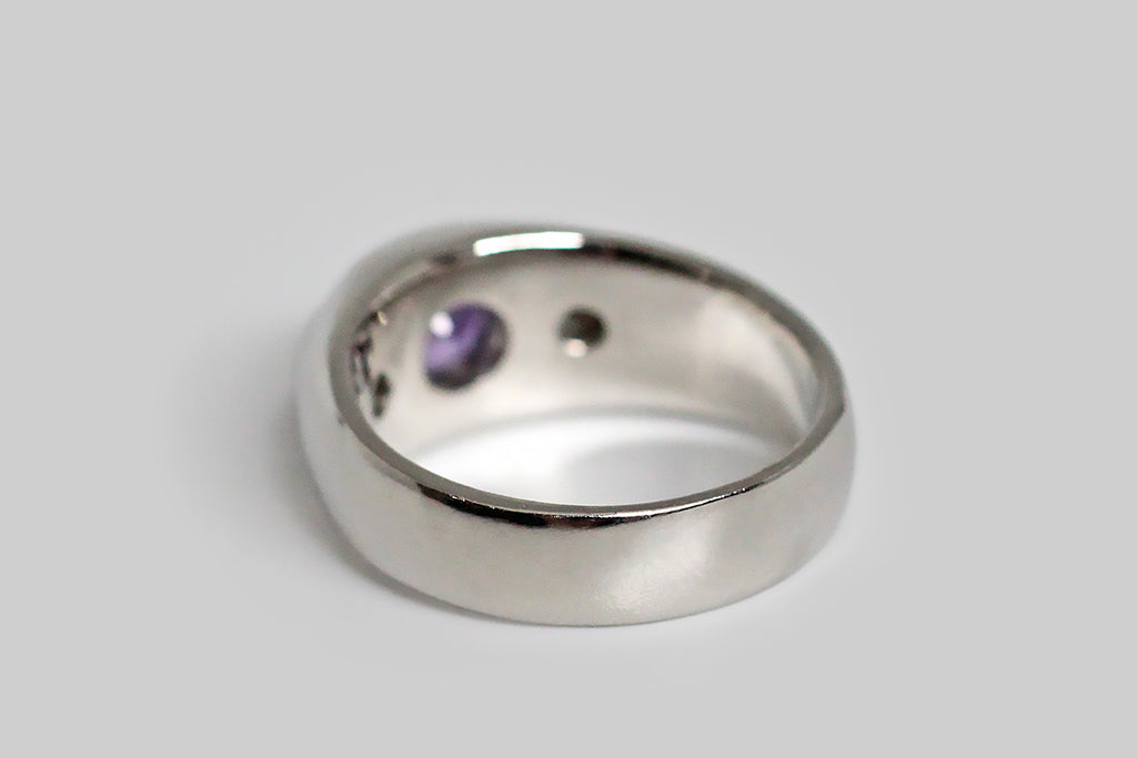 A classic, wide-band, three stone ring, modeled in platinum, whose primary gemstone is a striking natural sapphire. This 1.5 carat sapphire is flush set; its color is vibrant and unusual— a rich, evenly-saturated cool spectrum purple, with magenta inflections. It is flanked by a pair of high quality, flush-set, 1/4 carat, round brilliant cut diamonds (F/G, VS).