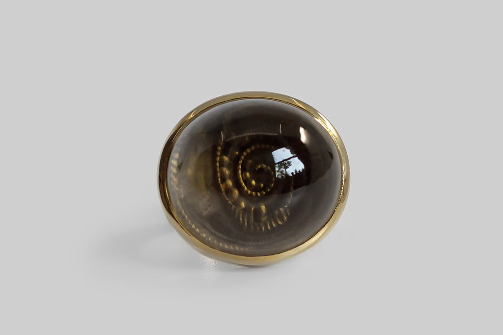 A mid 20th century ring, made by the well-loved Finnish modernist Bertel Gardberg. This ring is, at first glance, bold and minimal, featuring a high dome smoky quartz cabochon that is softly oval, oriented east west, and mounted in a smooth bezel, atop a weighty flat-wire shank. The ring's complex secret is the miniature dexterity game that lies beneath the quartz cabochon— movement causes the small gold balls to move along the maze's dotted spiral tracks, and the magnifying quality of the quartz creates co