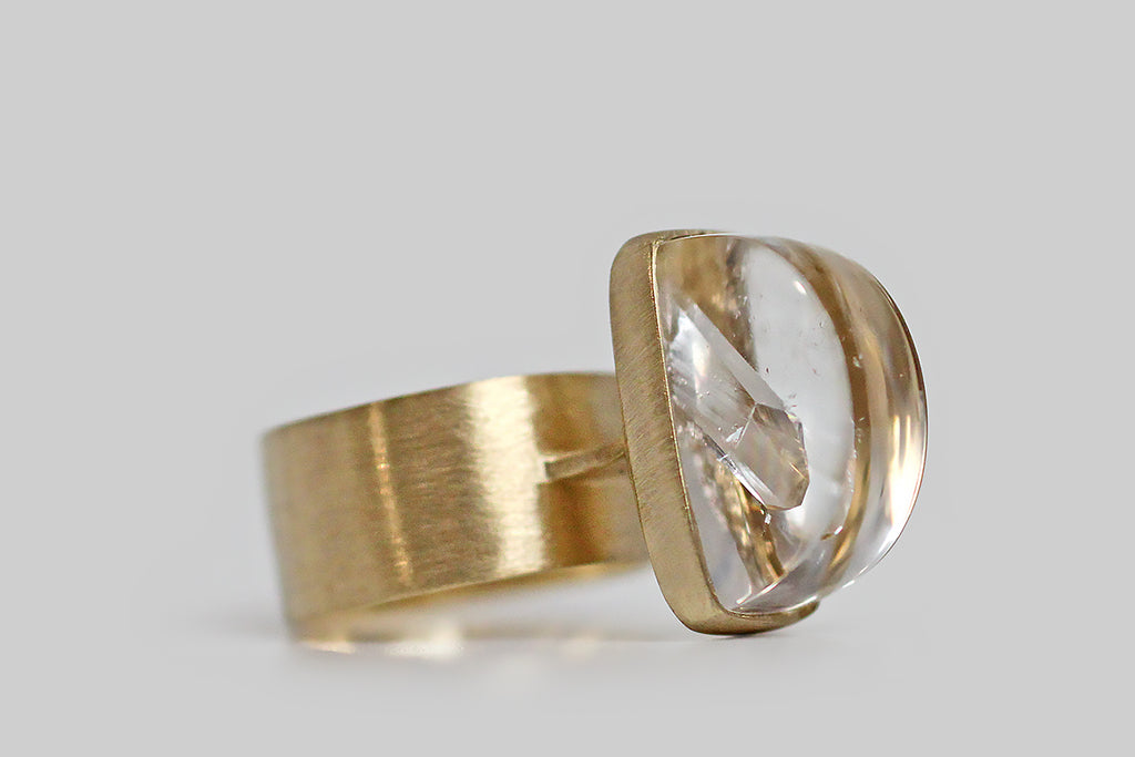 "A big, mystical, modernist ring, modeled in 14k yellow gold, that features a rare, axe-head-shaped quartz-in-quartz cabochon. The ""mother"" quartz, here, is especially fine and optically clear— it holds within it a beautifully formed, iridescent, quartz crystal point that grew into the clear host. This inspiring specimen is mounted north to south, and is seated in a full bezel— it perches atop a shapely, flat pier that connects the ring's head to its wide, flat band."