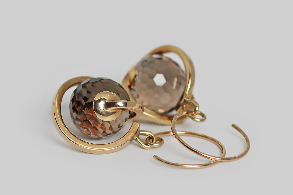 An unusual pair of kinetic earrings, modeled in 14k yellow gold, whose smoky quartz spheres are covered with many, small, hexagon-shaped facets, for extreme light play. These sparkling quartz gems turn freely inside the hand-fabricated, orrery-like mounts, which swing below their earwires. These earrings read like sparkling, ringed planets. The stylized, round, French hooks reflect that spinning aesthetic. These are fun, and eye-catching, with a great warm-neutral color palate.
