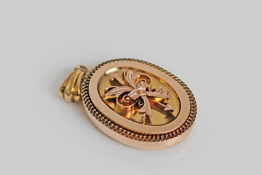A large, Victorian-era locket, modeled in two colors of 14k gold (yellow and rose), and decorated with a central, hand-pierced, quiver motif. This raised, three-dimensional quiver holds a pair of arrows and a pair of ribbons. It is especially lovely (and interesting) that the arrows point in different directions, one to the north and one to the south, as if some matter of the heart remained in question.