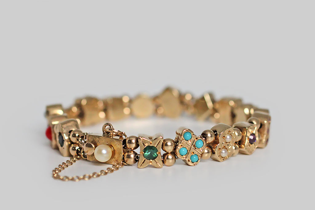 A charming 1940s slide charm bracelet, whose closely proportioned, gem-set charms are each a different geometric shape, and whose gemstones are placed like pips on card faces. These chunky little charms slide along the bracelet's two lengths of gold cable chain, separated by pairs of gold spacer beads— they feature a colorful variety of gemstones: sapphire, opal, turquoise glass, amethyst, blue and white zircon, coral, pearl, ruby and garnet.
