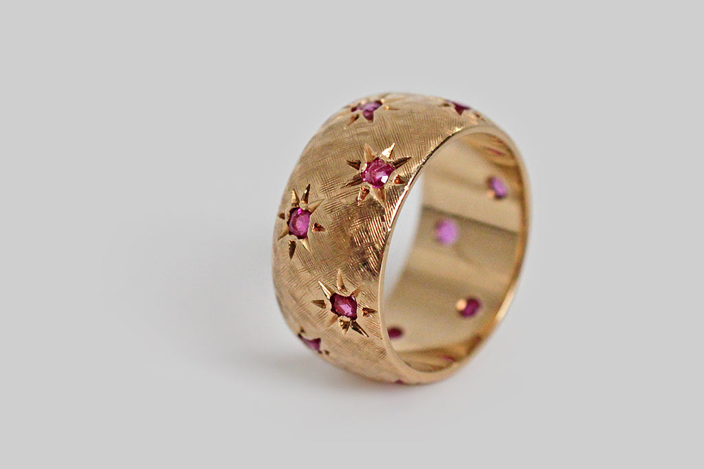"A wide 1940s band, modeled in rose gold with scattered, hand-graved seats made in the style of ""gypsy stars."" Each of these stars is set with a small, natural ruby— there are twelve, in total. This band has a hand-textured Florentine finish, which gives it a beyond-satiny feel and a very subtle visual texture."
