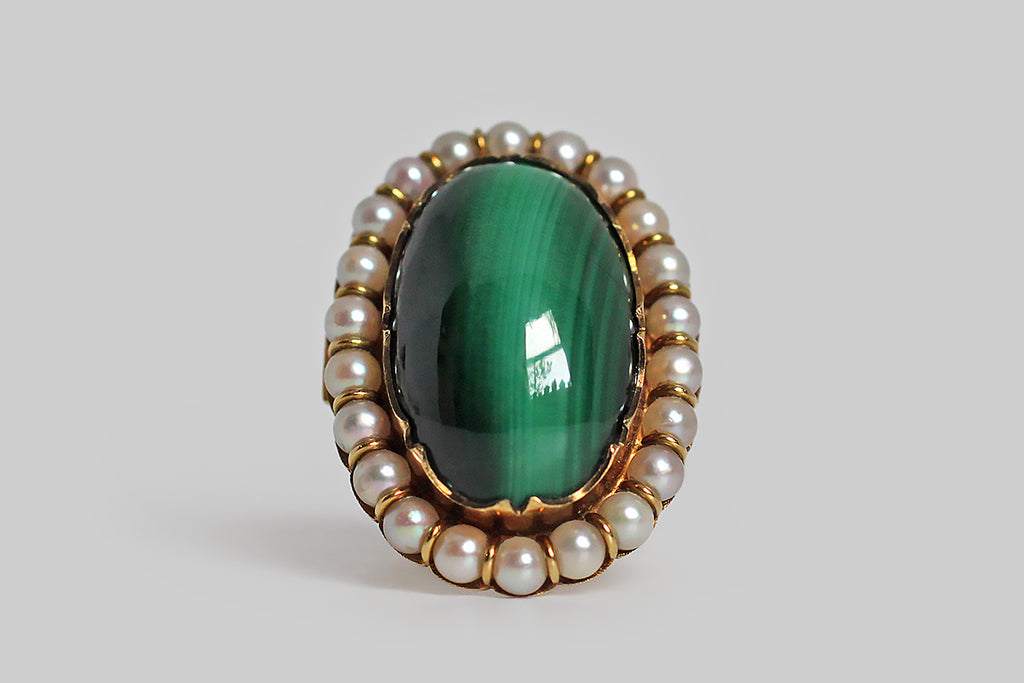 "A mid-twentieth-century cocktail ring, made in 14k yellow gold and set with a large, striking, malachite cabochon. This beautifully striated stone has a high, glassy polish— it sits inside an ornately-scalloped bezel, surround by a halo of iridescent white pearls. This gem exhibits a chatoyant ""cat's eye"" effect, which is uncommon in malachite. The ring's under-gallery is smooth and slightly bulbous; its shoulders are decorated with a subtle crosshatched texture. Victorian Revival"