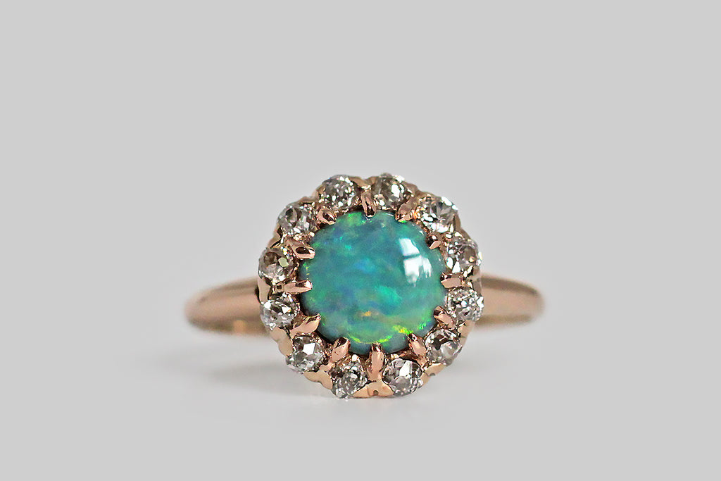 A heart-winning, Victorian-era, opal and diamond ring, modeled in 14k rose gold, whose central, blue opal cabochon is held in twelve, slender, hand-formed prongs. This round opal has a vibrant blue-green body tone and its patches of fire present in brilliant hues of green, yellow and red. The opal is framed by a sparkling halo of chunky little old mine cut diamonds.