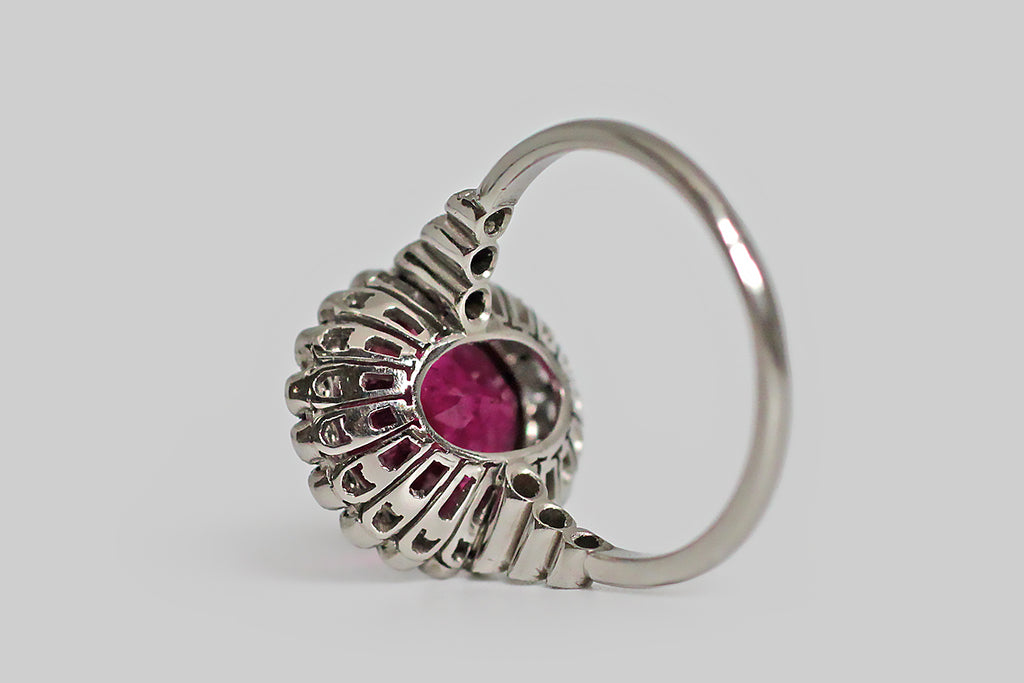 A vibrant, mid-20th-century cocktail ring, modeled in platinum and featuring a large, oval, rubellite tourmaline. This raspberry-colored gem is set in a smooth bezel, where it rests encircled by a series of small, bezel-set, brilliant cut white diamonds. Each of these dainty bezels is finished with a fine milgrained edge. The ring's undergallery is bulbous and decoratively pieced.