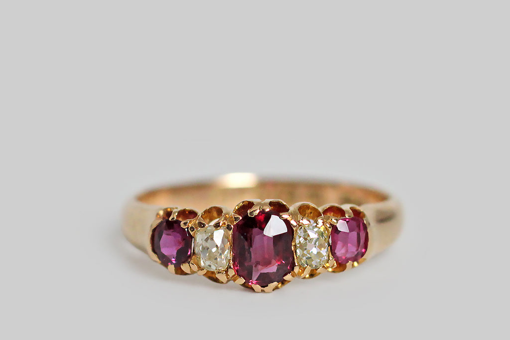 A darling, Victorian-era, five stone ring, modeled in 18k rosy yellow gold, with a tapering profile. This ring is set with three, vibrant, natural, rubies (.60 CTW) and two, cushion-shaped, old mine cut diamonds (.30 CTW)— these gemstones graduate in size, with the largest resting at the center. They are held in sculpted, split-prongs that are integral to the ring's subtly-lobed, scalloped gallery. The ring's substaintial half-round shank tapers, somewhat, toward the base.