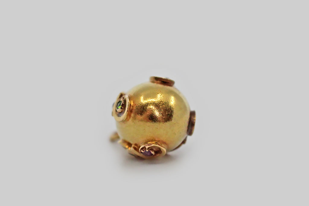 A lovely, Imperial Russian miniature egg pendant, made around the turn of the 20th century. This egg-shaped pendant is modeled in 56 zolotnik gold, and is decorated with a repeating double-spiral decor. These charming spirals are set with old cut demantiod garnets and rubies. This egg's primary loop is marked 56, for 56 zolotnik gold, and with the Fabergé workmaster's initials AK.