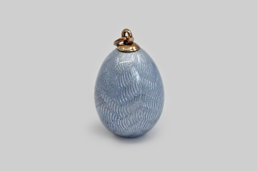 A lovely, Imperial Russian miniature egg pendant, made around the turn of the 20th century. This egg-shaped pendant is modeled in 56 zolotnik gold, and is decorated with fine, powder-blue guilloche enamel work, whose pattern resembles layered feathers or leaves. This little egg has a small six-pointed star on its bottom. We are confident that this egg belongs to the house of Fabergé