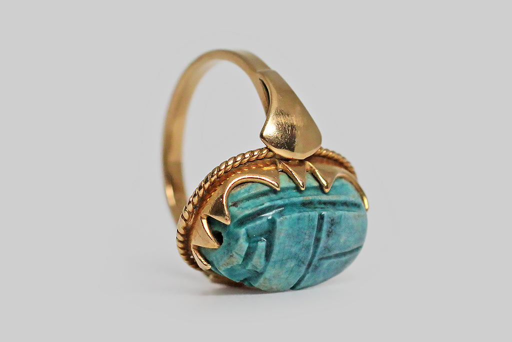 A magical, Art Deco era ring, modeled in 18k yellow gold and set with a brilliant blue, Egyptian, faience scarab bead. This talisman of renewal and rebirth is held in an ornately scalloped bezel. The foot of this festoon bezel is embellished with twisted gold wire, and the ring's shoulders are decorated with a shapely, very minimal, lotus motif.