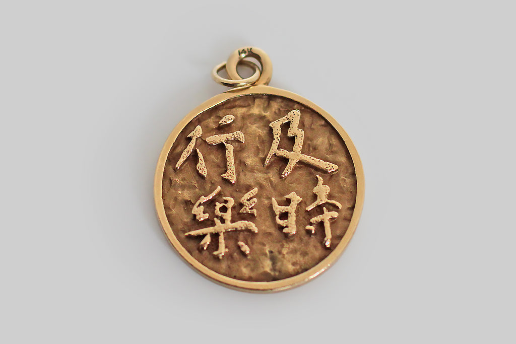 "A large, mid-twentieth-century charm, modeled in 14k yellow gold and decorated with Chinese characters that direct the wearer (or the viewer) to ""seek pleasure."" These are traditional characters— they are rendered in a manner that suggests brush strokes, and the handwriting of an individual."