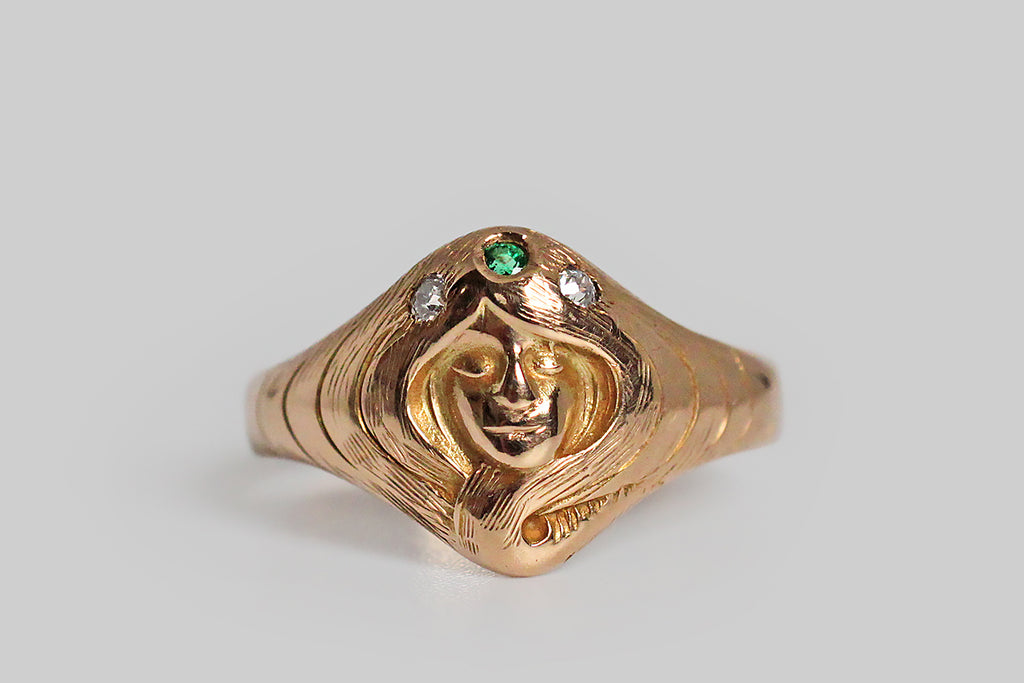 "A sweet and soulful Art Nouveau era ring, whose face is the face of a dreamy ""gypsy"" girl, surrounded by the swirling waves of her own long hair. Our girl wears a serene expression, and a crown of three small gems— a natural emerald and two mine cut diamonds. Her face is beautifully carved and fished with a high polish; the engraved details of her hair extend into the shoulders the the ring shank, which tapers toward the base."