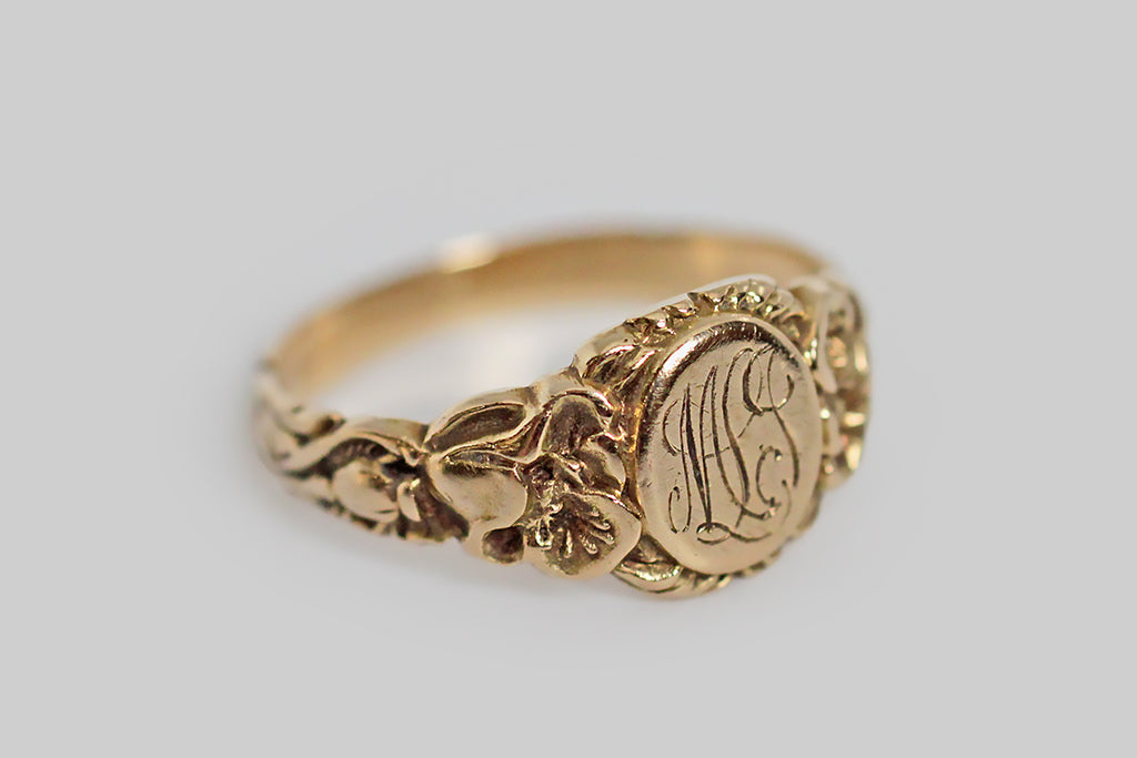 An antique, Art Nouveau era signet ring, made in 14k yellow gold, with ornate, carved details that are especially well-preserved. The ring's shoulders are adorned with a pair of realistic, fleshy poppies, whose toothed leaves travel down the ring shank to the base, where their stems twine together. Its round face is engraved with the monogram MLJ, in curling period script.