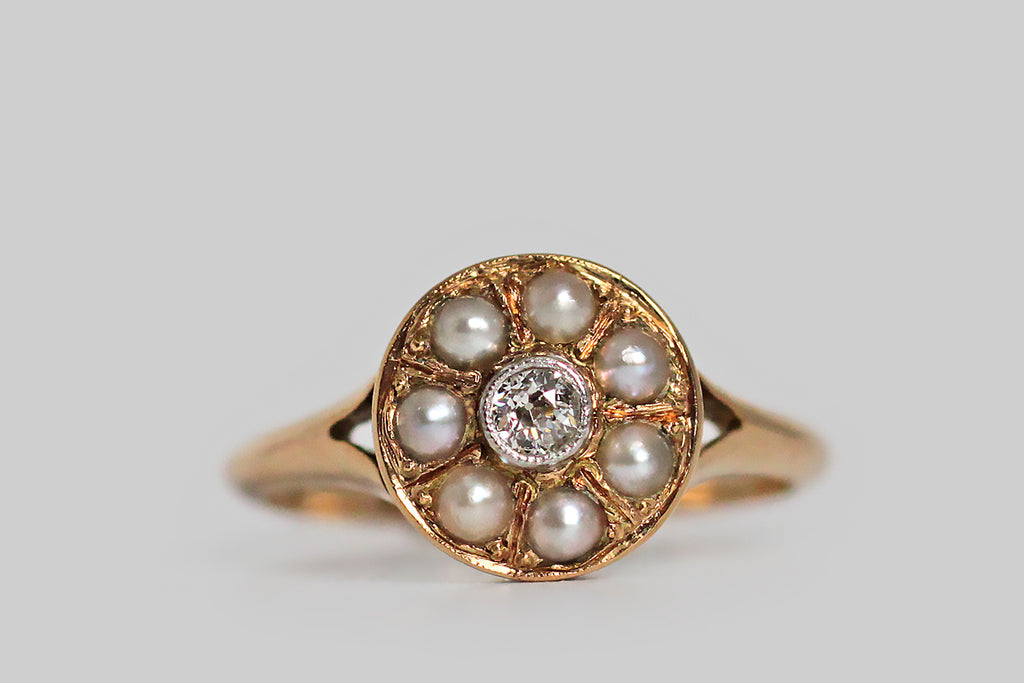 A darling, early-20th-century ring, modeled in rosy 14k yellow gold, whose central, old European cut diamond is set in a milgrained, platinum bezel, where it is surrounded by a halo of seven, natural, silvery-white half-pearls. The ring's shank is substantially made and is decoratively split at the shoulder— it tapers somewhat toward the base, and has an elegant knife-edge profile. The ring's scalloped cut-work gallery imparts a crown