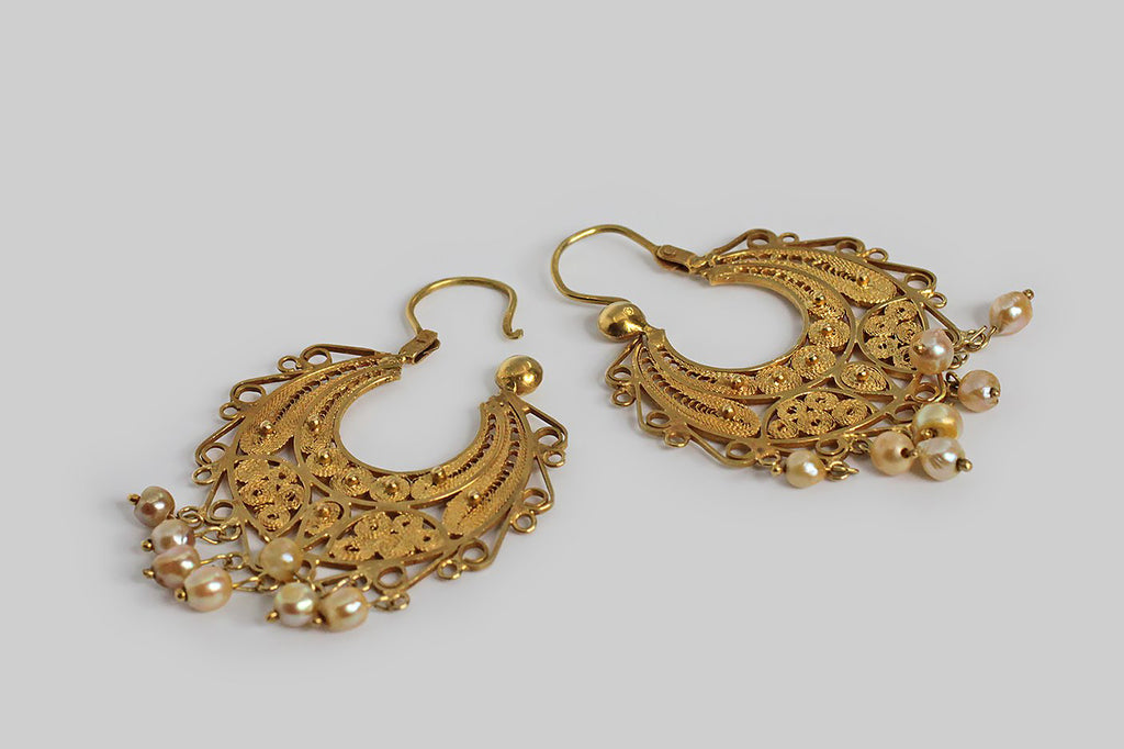 A powerfully romantic pair of Spanish colonial filigree crescent earrings, dating to the early 1800s. Made in yellow gold, with a fringe of natural, creamy, golden pearls, these substantial hoops feature the most precisely executed, nested, spiraling wirework and applied granulation— curls, paisleys, and and spirals abound! The ear wires are hand-formed, back-to-front threaders, with miraculous old hinges and a discreet ball-shaped catch.