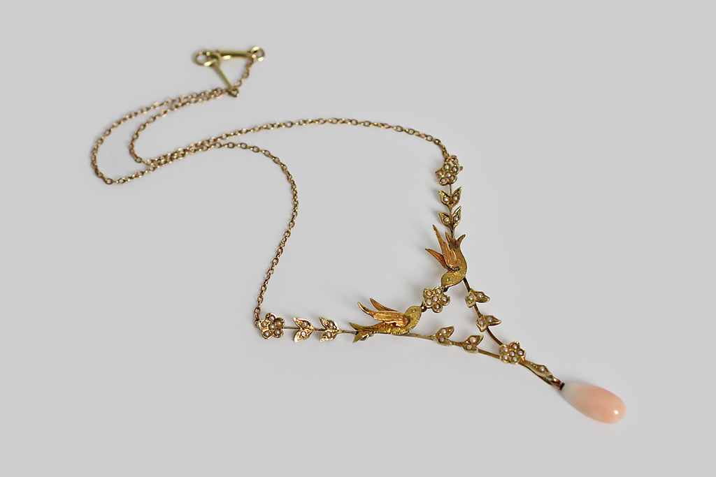 A Victorian-era necklace, with a sweet, serene presence. At its center, a pair of three-dimensional swallows come together to hold a five-petaled, pearl-set flower. An elegant, v-shaped framework of flowers and leaves is built beneath these bird friends, and a pair of jointed flowers attach them, from above, to the necklace's fine cable chain. All of the floral elements are set with natural seed pearls.