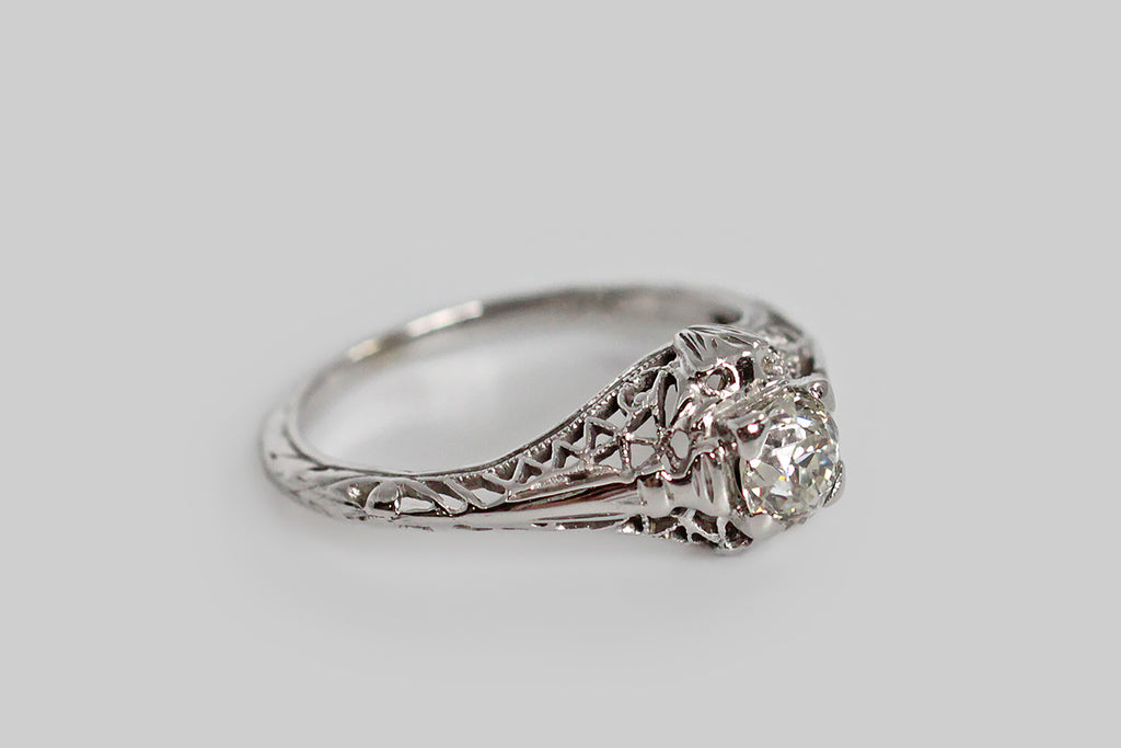 An Art Deco era engagement ring, made in 18k white gold and set with a charming, 1/3 carat, old mine cut diamond. This plump darling is held slightly aloft in four tab-style prongs. The lacy filigree setting is trellis-like, and features a small shield in its design, on either side of the gallery. There are many small, interesting details in this filigree and they are all fresh and crisp. The diamond is especially bright and lively.