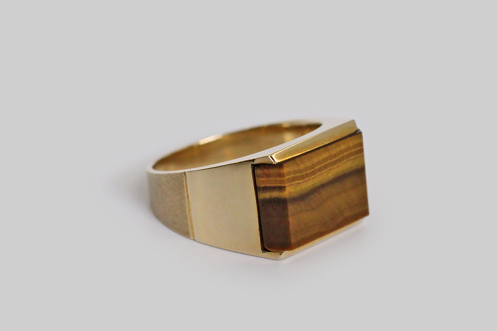 A weighty, vintage, modernist ring, dating to the mid 20th century, whose design reflects a minimalist aesthetic. This signet style ring's rectangular face features a highly-polished, flush-set, tiger's eye slab, held in a floating bezel. The ring's shank tapers from its broad shoulder, toward the base--- it has a clever bifurcated finish, that changes midway from high polish to deeply satin. A bold, monochromatic-gold jewel whose chatoyant centerpiece has hidden depths upon closer reflection. A minimalist