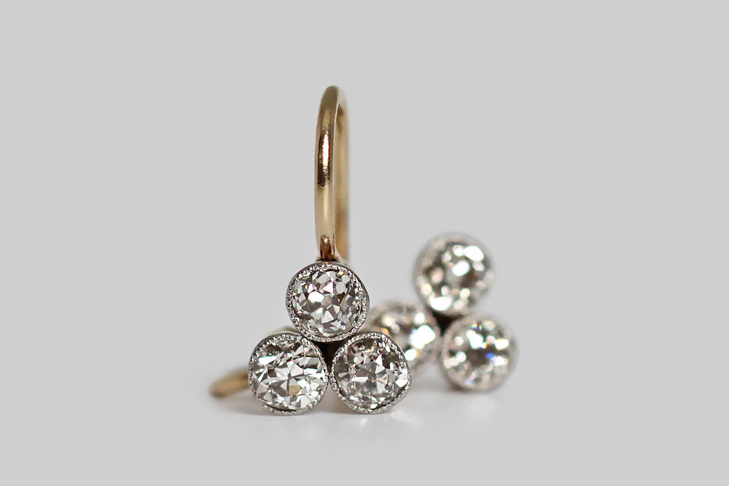 "A dainty pair of Edwardian era earrings, modeled in 18k yellow gold and platinum, whose trios of chunky, little old mine cut diamonds are arranged in a trefoil or clover shape.  These petite earrings drop just below the earlobe— they would have originally been the top elements for a pair of longer, more ""dramatic"" earrings. On their own, they are elegant and sparkly, and the perfect size for daily wear."