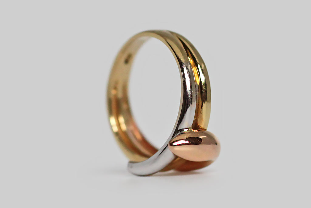 A vintage snake ring, with a serene, minimalist presence, modeled in three colors of 18k gold. This sweet, dignified serpent wraps the finger three times, and each of its three colors (rose, yellow, and white) are especially vibrant. Snakes have long been regarded as guardians, so this ring makes a lovely statement as a protective amulet. It is also flattering in wear and very comfortable, making it an ideal alternative wedding band.