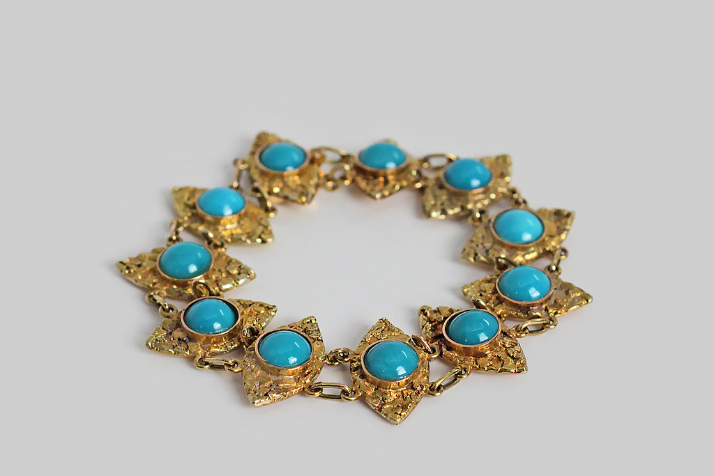 An antique bracelet, whose navette-shaped, turquoise-set links read like a series of vigilant eyes. Each of these beautiful links is designed with a substantial overlay of natural gold nuggets— the base of each navette is warm 14k yellow gold, as are the hand-fabricated rings that connect the links. The central centerpiece of each link in this bracelet is a brilliant blue turquoise cabochon.