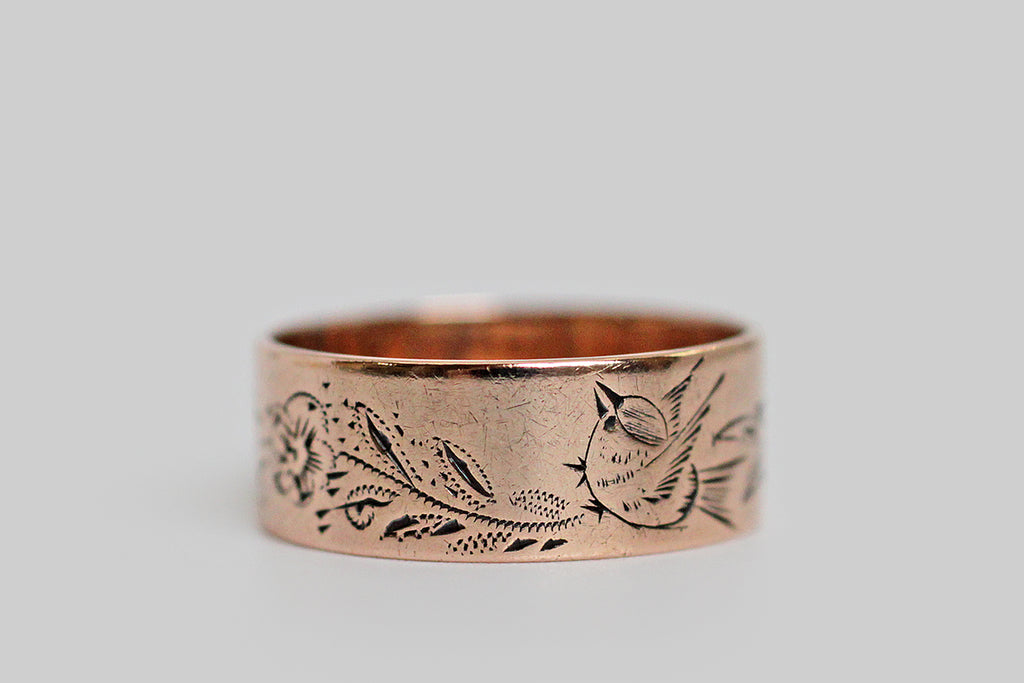 A Victorian era wedding band, made in 14k rose gold and hand-engraved with the most adorable little swallow. Our cheerful fellow is all puffed up with song, and surrounded by florals sprays. This charming engraved motif covers the entire surface of the ring, without breaking, so you get two bird friends. The graphic quality of this ring's engraving is especially sweet and character-rich among its contemporaries. The ring is marked 14, and is inscribed M.E.M. is curling period script.