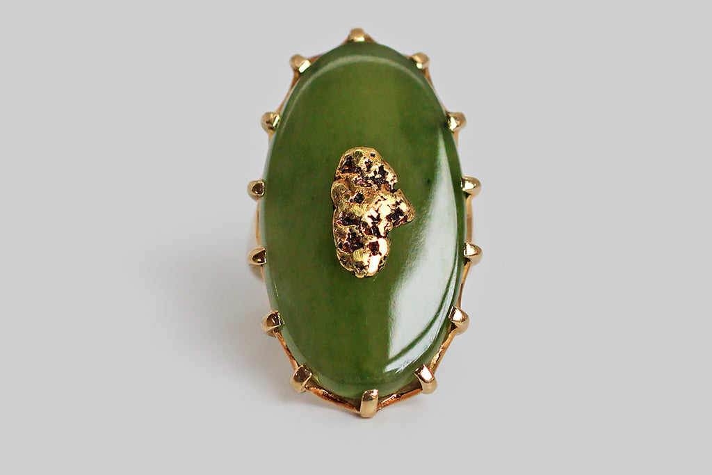 A dramatic vintage ring, modeled in 10k yellow gold, featuring a large, oval, nephrite jade cabochon, upon which a shapely, natural gold nugget is mounted. Our luminous slab of moss-green jade is held in the ring's crown-like, fourteen-prong head. The nugget is riveted to the jade, so that it appears to float in a green field. The ring's gallery is scalloped and carved to accentuate the prongs.
