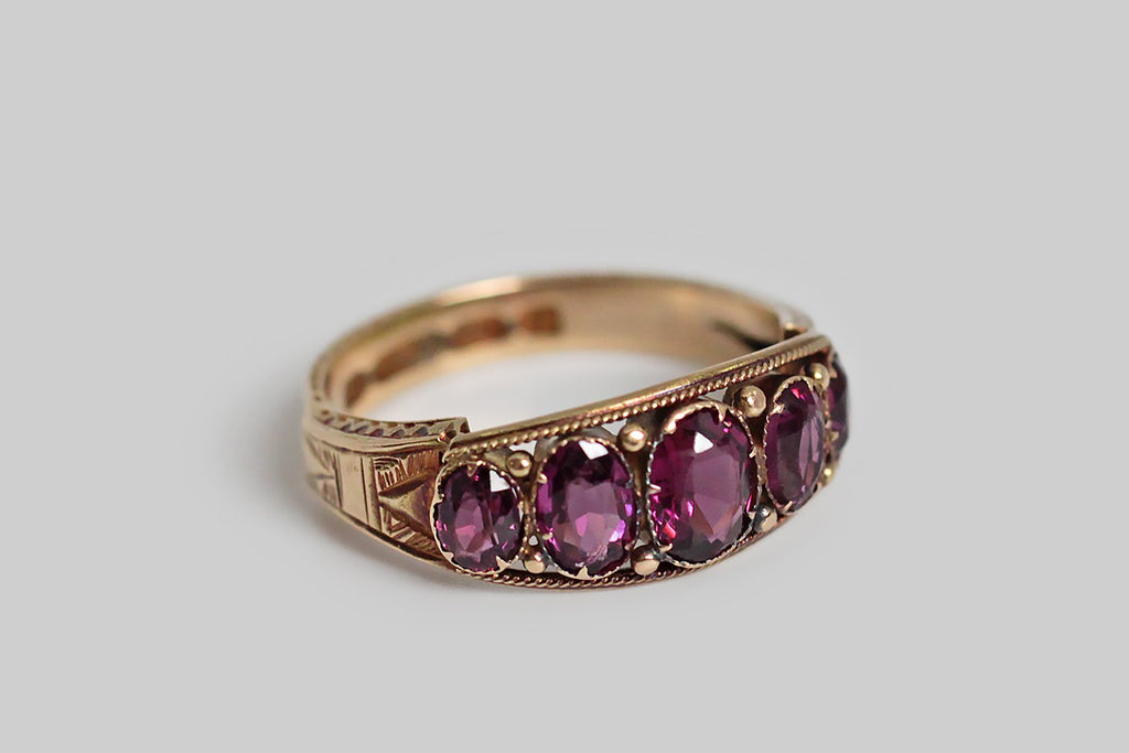 A Victorian-era five stone ring, set with a suite of faceted grape garnets. These oval gemstones graduate in size and are set in pronged bezels— decorative gold spheres adorn the spaces between these bezels, and the ring face is framed by a twist border.