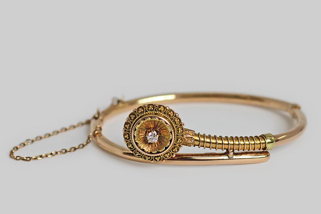 A hinged, Victorian-era, Etruscan revival bangle bracelet, made in yellow gold, and set with an old European cut diamond. This bangle features a highly-dimensional, beautifully-carved flower-like head, surrounded by finely-executed gold granulation and rope work. The hinge and the push clasp function perfectly, and the safety chain is original.