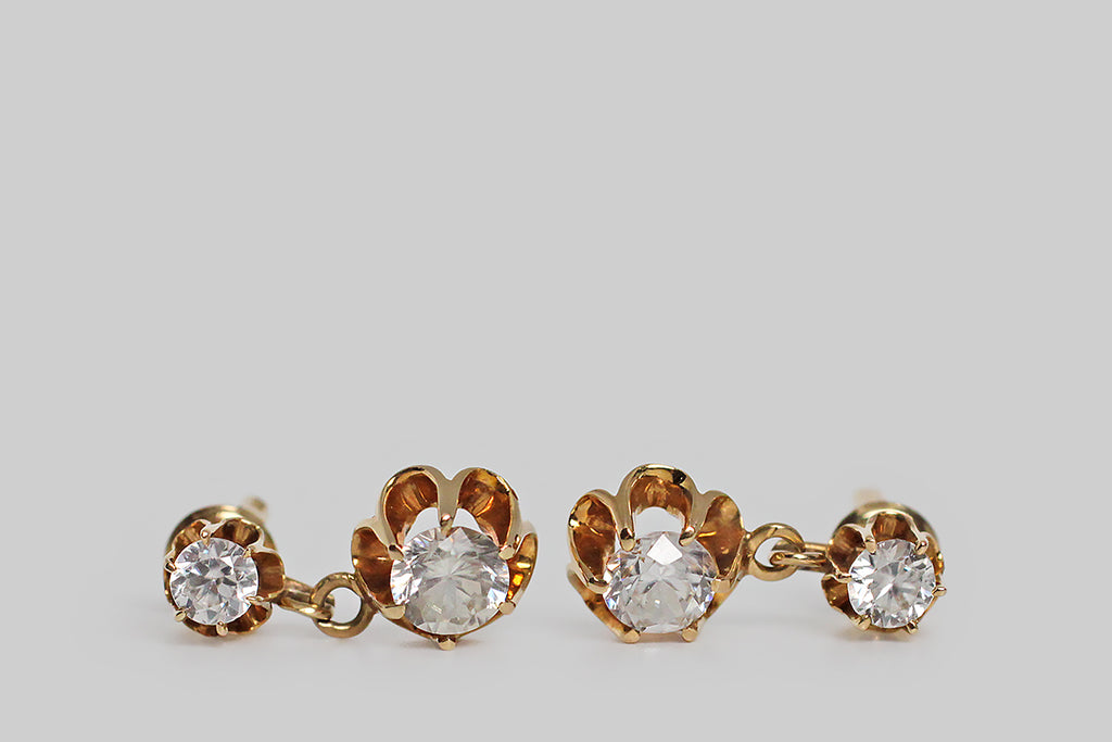 A pair of late-Victorian drop earrings, modeled in 14k yellow gold, whose buttercup mounts hold a plump suite of sparkling paste stones. These vibrant old imposters look very much like real diamonds, thanks to their hand-cut nature. The buttercup settings are designed with dramatic, rounded, cutaway sections, and six claw-like prong that hold the paste gems aloft. These earrings are short drops