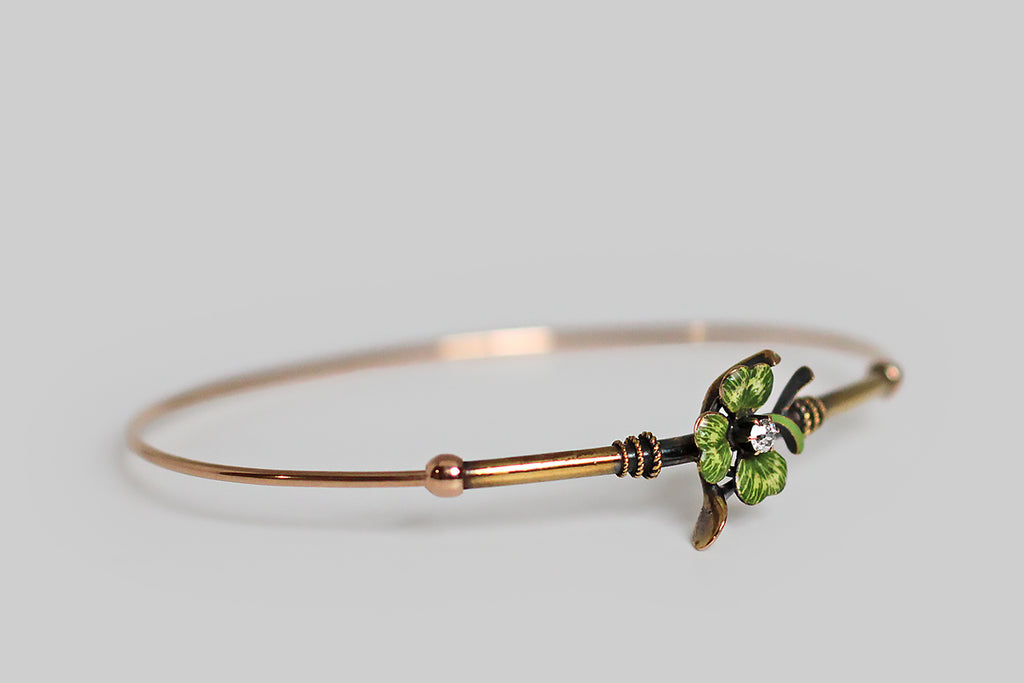 A slender, Victorian-era bangle bracelet, modeled in 14k gold, whose face is adorned with two good luck charms— a wishbone and a beautifully hand painted, polychrome enamel clover. A .10 carat old mine cut diamond rests, in claw-like prongs, at the center of this lucky composition. Trios of graduated rope details encircle the gold tube that comprises the bracelet face, where they flank the bracelet's figural centerpiece.