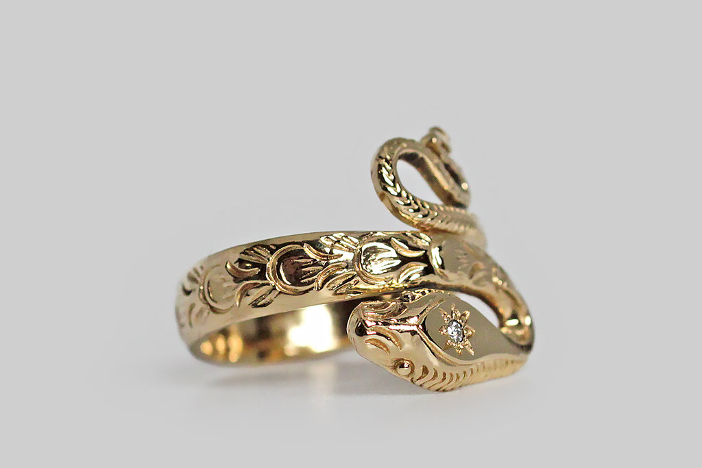 A highly-detailed, early 20th century, Victorian revival snake ring, modeled in 14k yellow gold (bypass style) to wrap the finger. This weighty, sinuous darling wears a peaceful expression, and her body is decorated with a striking pattern of flower-like scales. Our snake friend is crowned with a deeply-graved, diamond-set star; her face and tail are also ornately carved and both lay against the finger in graceful meandering curves. Marked 14k for purity.