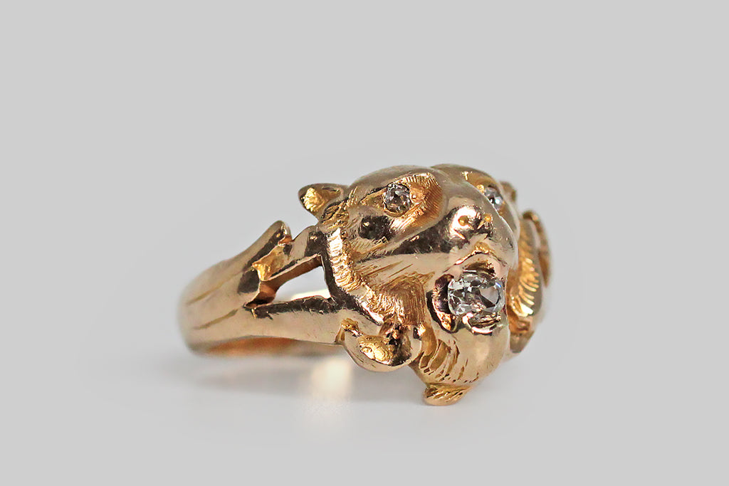 A weighty, Victorian-era, tiger mask ring, modeled in 14k yellow gold, whose subject holds a .20 carat old mine cut diamond in his open mouth. This fierce, roaring fellow has a lovely face that, though time-worn, retains its important features and textures. Our beastie's watchful eyes are also set with small, glinting, old mine cut diamonds. The ring's half-round shank is carved with bold, dimensional flourishes at the shoulder, and it tapers toward the base.