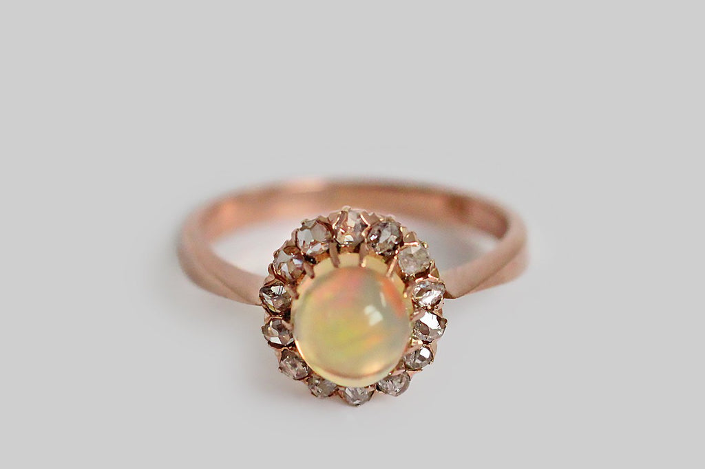 A darling, Victorian-era, opal and diamond ring, made in 12k rose gold, whose central, translucent opal cabochon is held aloft in fourteen, slender, hand-formed prongs. This water opal has a warm golden tone and its fire is primarily red, gold and vibrant absinth green. The opal is framed by a glinting halo of prong-set, rose cut diamonds. This ring has an ornate crown-like gallery. Its shank is narrow at the shoulder, widening toward the base. Marked with a 12 to indicate metal purity.