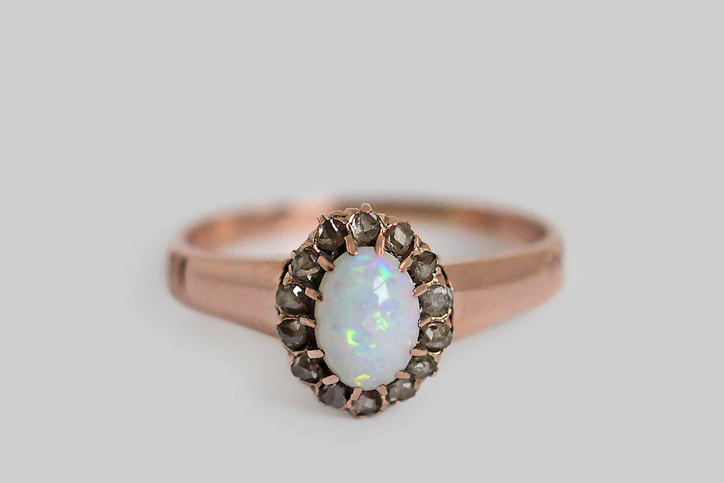 A darling, Victorian-era, opal and diamond ring, made in 12k rose gold, whose central, white opal cabochon is held in fourteen, slender, hand-formed prongs. This opal has a bright, blue-white tone and its rainbow-colored fire presents in a scattered, confetti pattern. The opal is framed by a glinting halo of silvery, prong-set, rose cut diamonds.