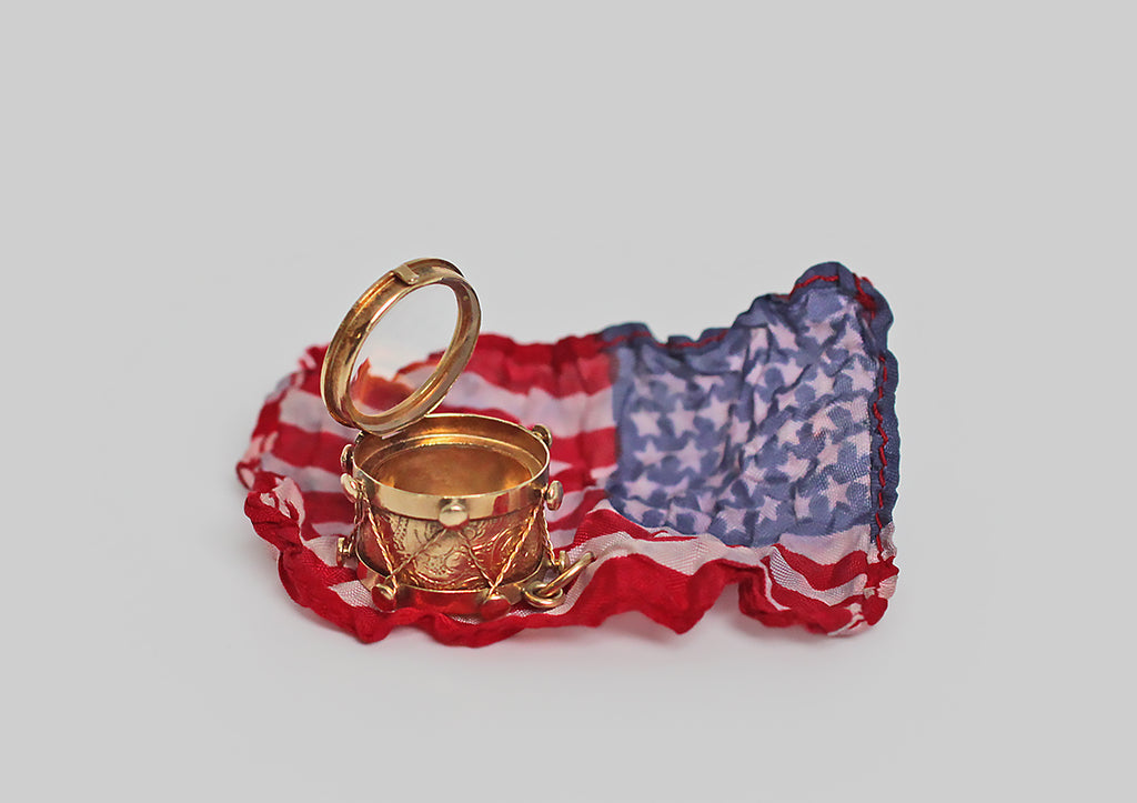 An unusual WW1 (Edwardian) era watch fob, modeled as a highly realistic rope-and-tension snare drum. This 14k gold drum has a lightly-domed glass front that opens to reveal a compartment, made to hold a miniature, folded, 48-star American flag. The reverse drum face is a set with an iridescent mother of pearl disc.