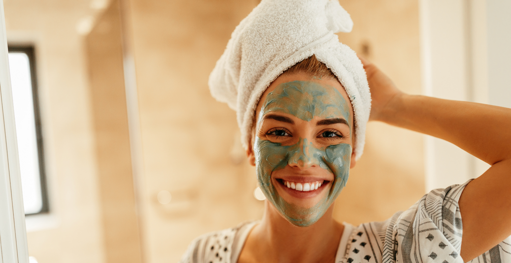Woman with face mask on and towel in hair