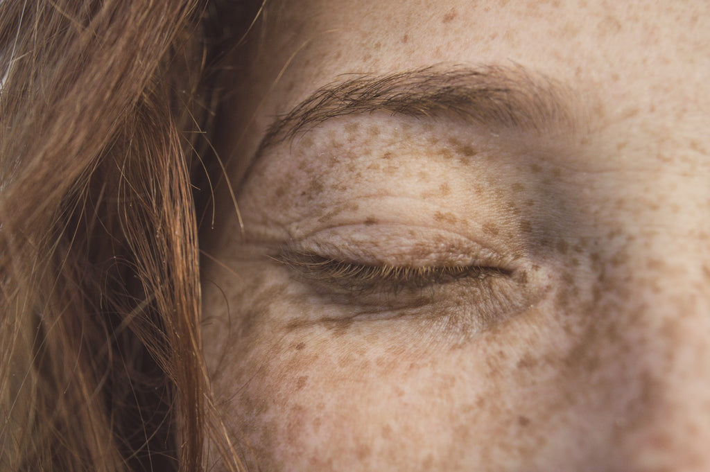 close up of woman's eye with freckles