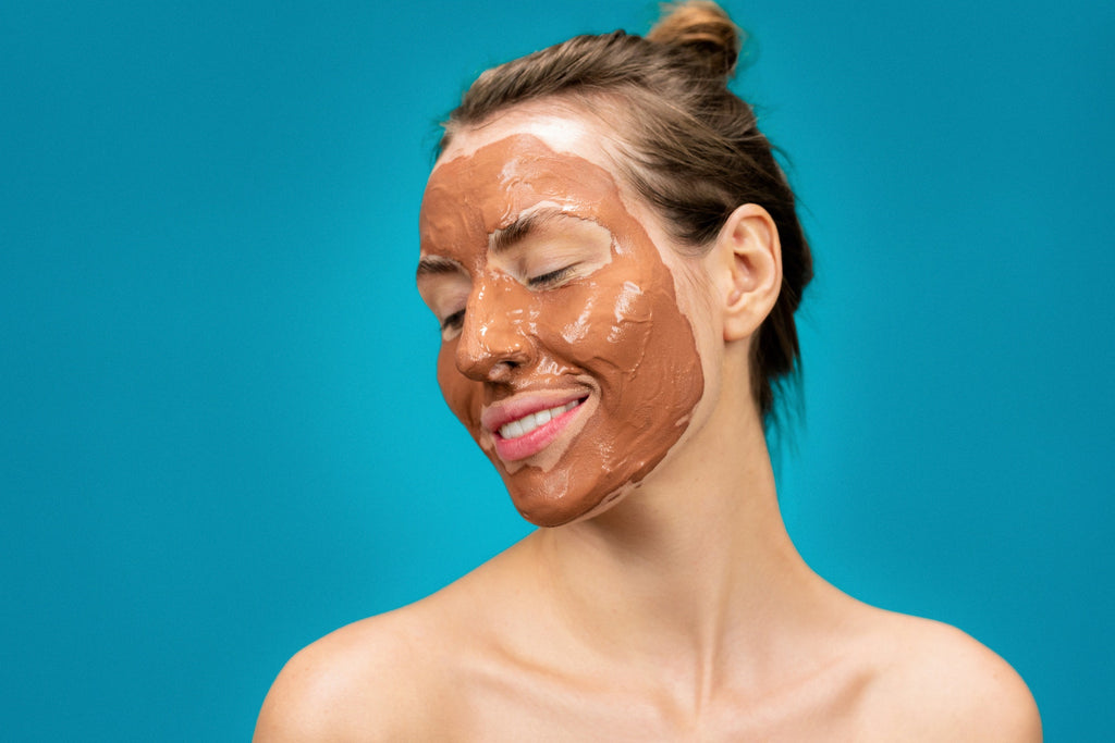 woman smiling with skincare face mask on
