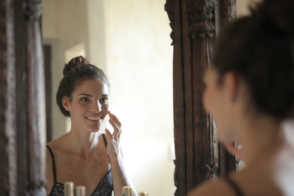 Woman with clear skin looking in mirror using skincare products for acne