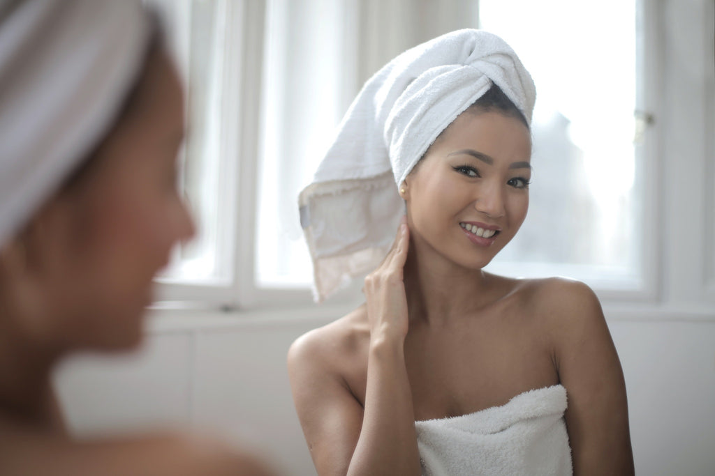 Woman looking in mirror after using Matrixyl 3000 skincare product