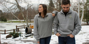 Woman and man modeling Hamburg Brewing branded gray quarter zip sweatshirts outdoors