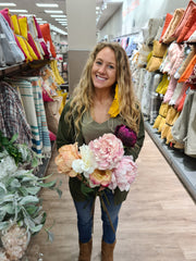 Blonde KoKo owner holding bunch of artificial flowers