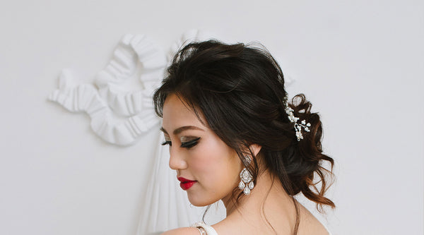 Woman with statement earrings and bridal headpiece