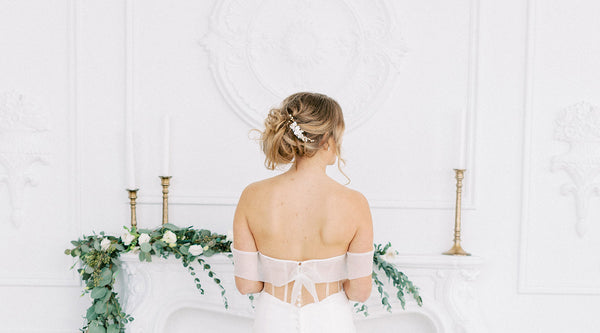 bride standing at mantle with greenery and candlesticks