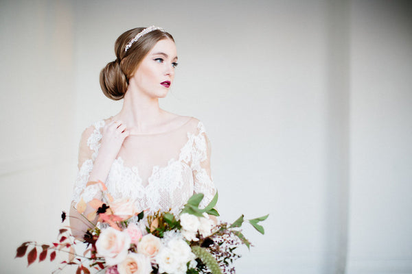 bride wearing a headpiece and holding a flower bouquet