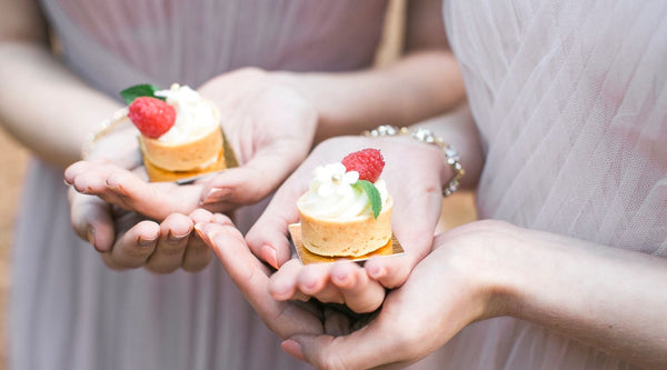 two bridesmaids holding cupcakes