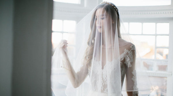 bride standing by the window in a veil covering face