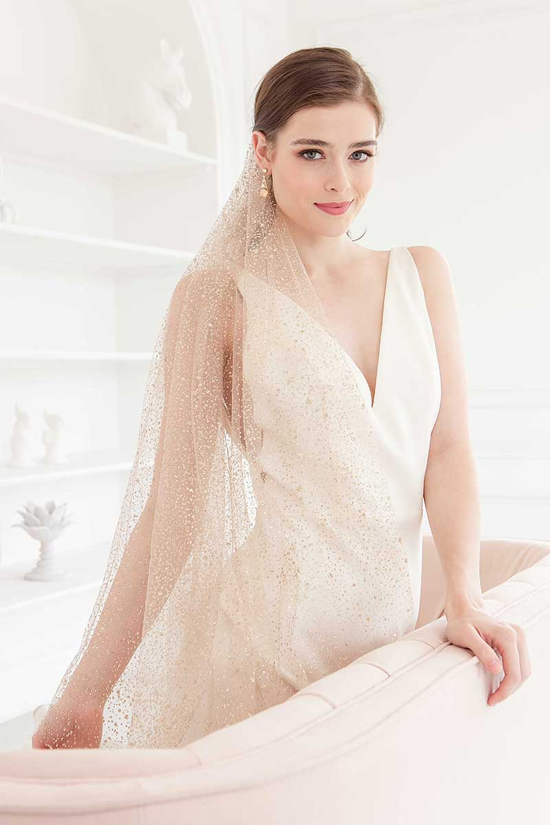 Bride standing at sofa wearing rose gold glitter veil and modern minimal wedding dress